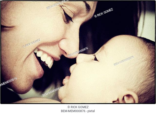 Hispanic mother touching noses with baby
