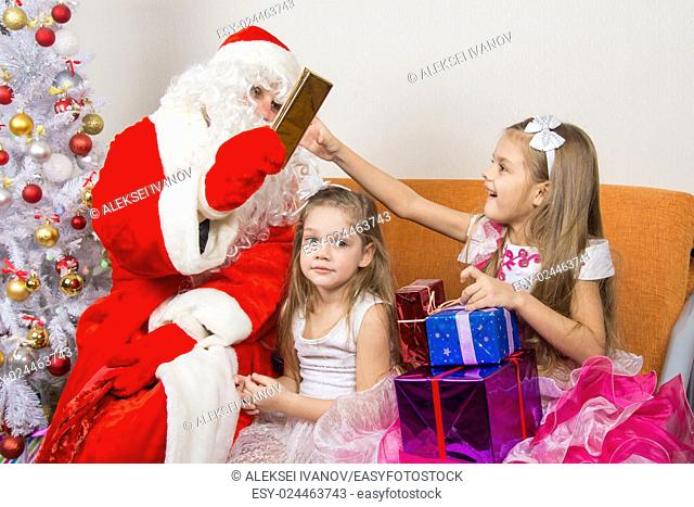 Santa Claus gives gifts to one girl, the other sitting in the waiting