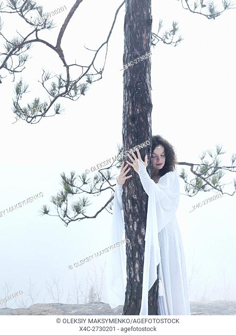 Young woman in white dress hugging a pine tree. Reconnecting with the nature