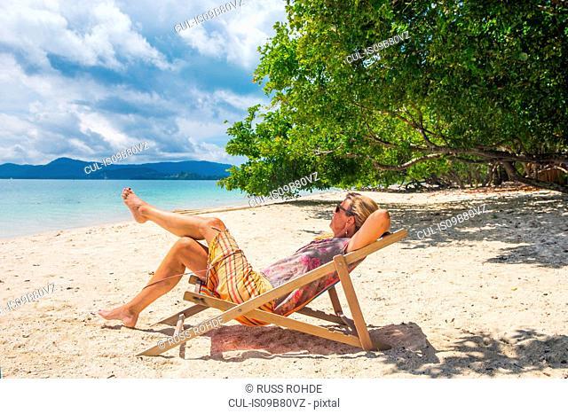 Woman reclining in deckchair on beach, Koh Rang Yai, Thailand, Asia