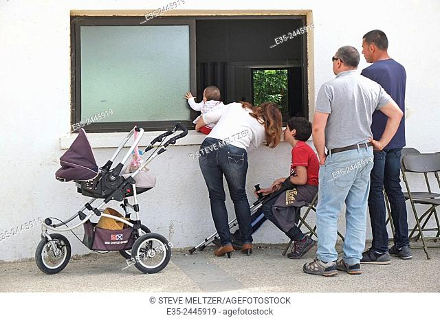 A family watches a wedding from outside a chapel