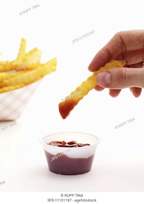 Hand Dipping a French Fry into Ketchup