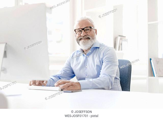 Smiling mature man with beard and glasses at desk