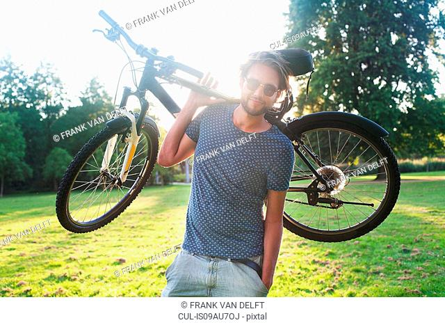 Portrait of young man carrying his bicycle in park at sunset