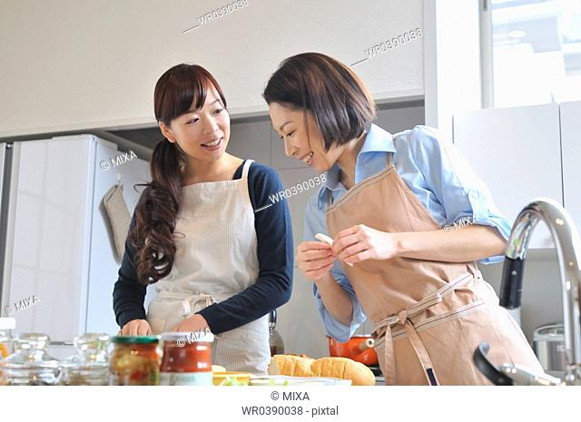 Two mid adult women cooking in the kitchen