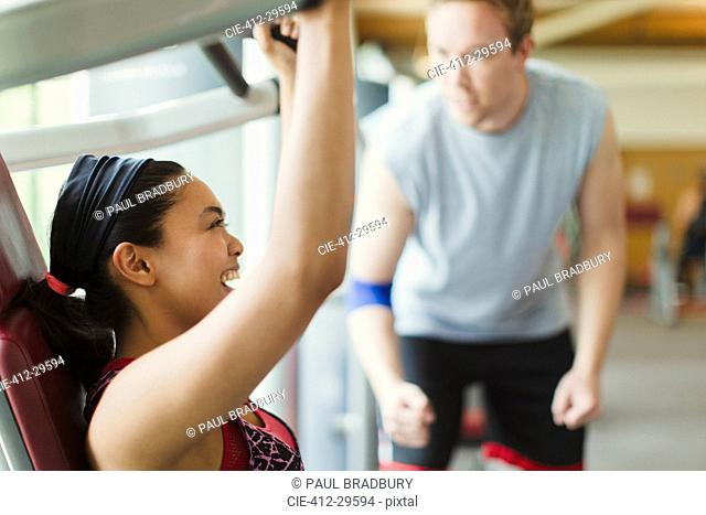 Personal trainer guiding enthusiastic woman using exercise equipment at gym