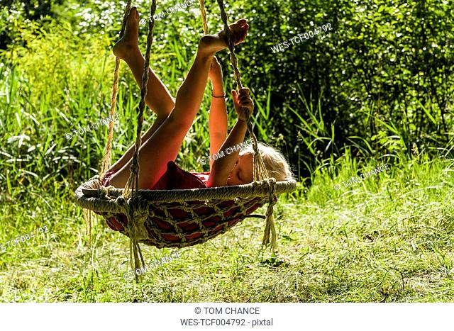 Girl relaxing in nest swing