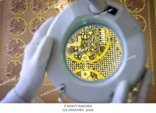 Yellow circuit board under inspection magnifier in circuit board factory