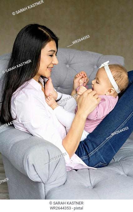 Mother is sitting with baby on an armchair