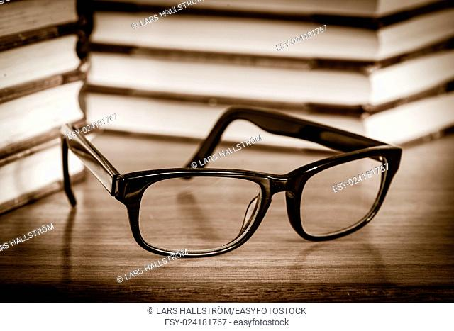 Eyeglasses lying on table with stacks of book in the background. Concept of education, reading literature or studying hard
