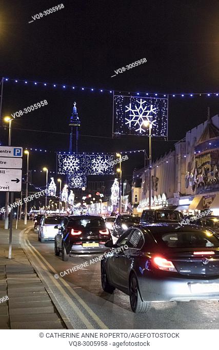 Car tail lights driving along the Esplanade through Christmas snowflake and Big Ben illuminations towards Blackpool Tower, Blackpool, England