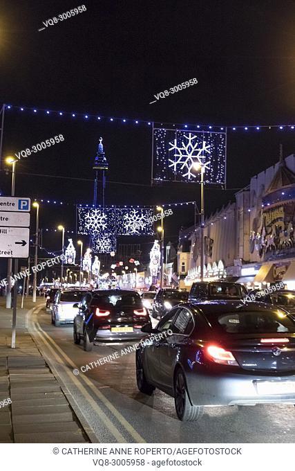 Car tail lights driving along the Esplanade through Christmas snowflake and Big Ben illuminations towards Blackpool Tower, Blackpool, England