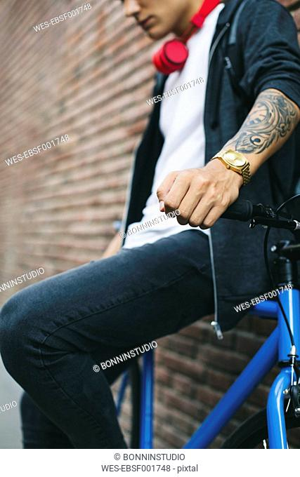 Teenager with a fixie bike, golden clock and tattoo on forearm
