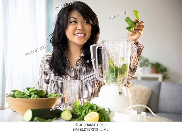 Pacific Islander woman making green smoothie in blender