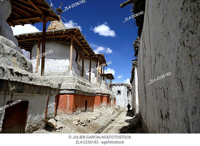 Silhouette of a man in a street with stupa (chorten) in the walled city of Lo Manthang, the historical capital of the Kingdom of Lo