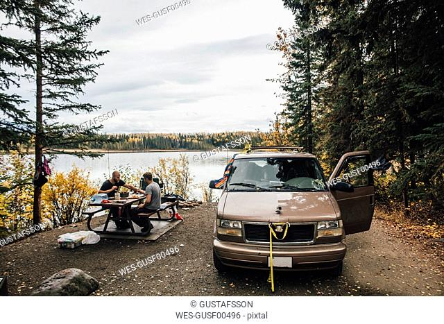 Canada, British Columbia, friends with minivan resting at Boya Lake