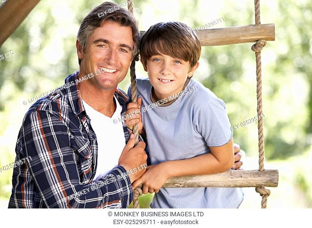 Father And Son In Garden By Treehouse