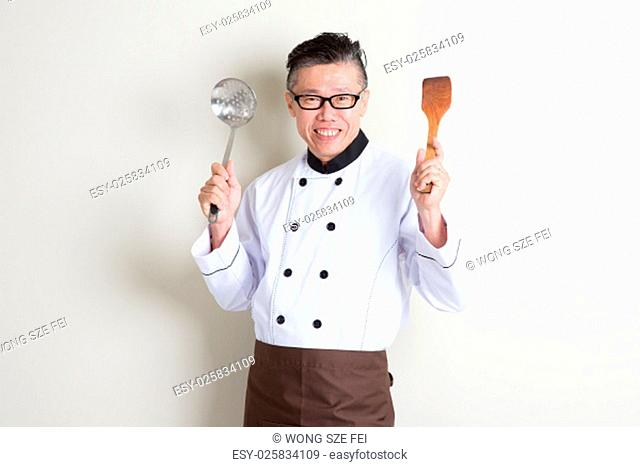 Portrait of confident 50s mature Asian male chef in uniform hands holding kitchen tools and smiling, standing on plain background with shadow, copy space