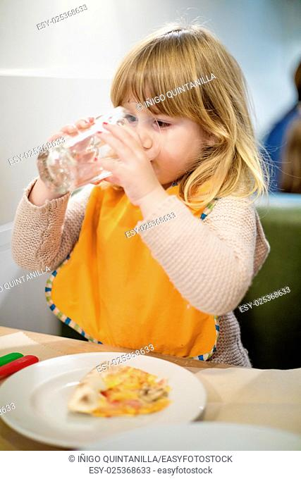 portrait of three years old blonde caucasian child with orange bib drinking water in crystal glass at pizza restaurant