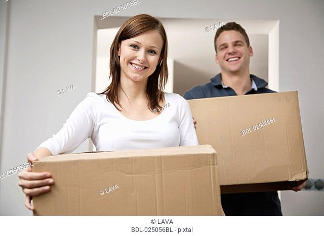 young couple carrying moving boxes