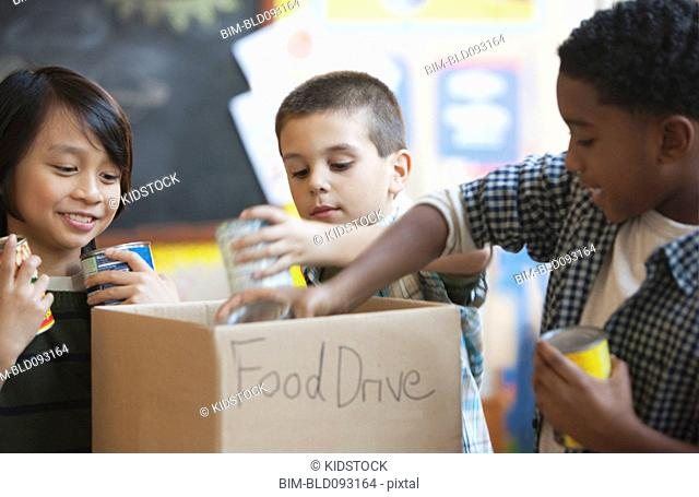 Boys packing box with food for school food drive