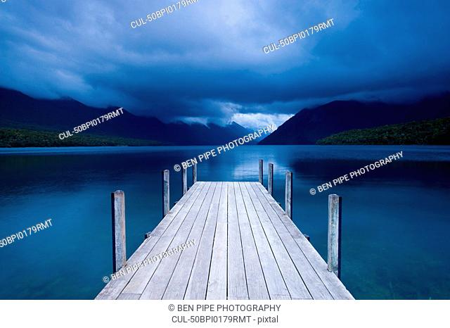 Wooden pier stretching into still lake