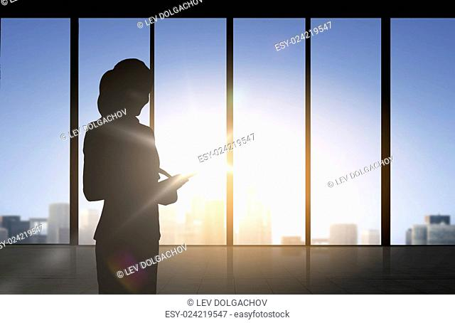 business and people concept - silhouette of woman with tablet pc over office window background