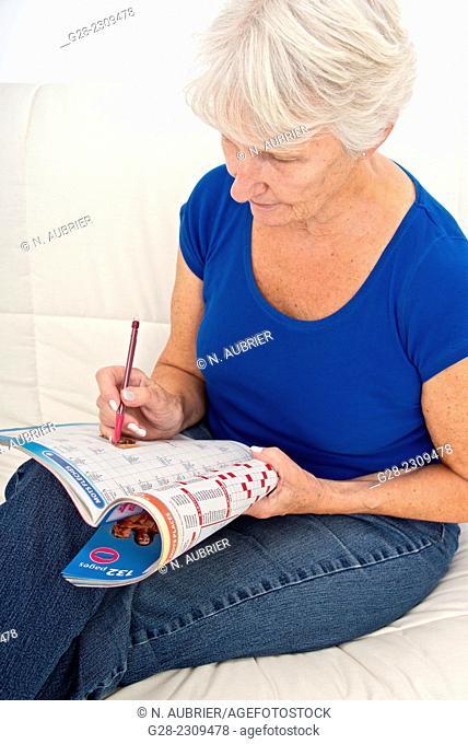 Senior woman in blue, exercising her brain for Alzheimer doing crosswords