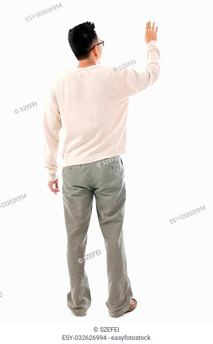 Rear view of Asian man hand touching on transparent virtual screen, space for text/button, full length standing isolated on white background