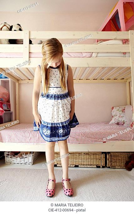 Girl wearing dress and looking down at polka-dot shoes