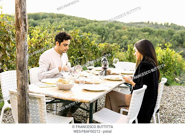 Italy, Tuscany, Siena, young couple having dinner in a vineyard
