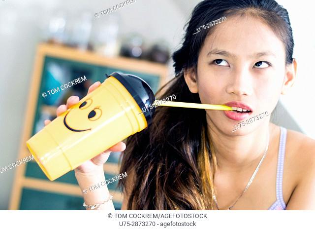 Young attractive Asian woman with novelty smiley plastic cup in an indoors setting