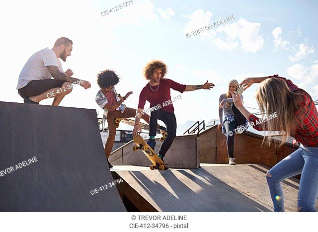 Woman photographing male friends skateboarding on ramp at sunny skate park