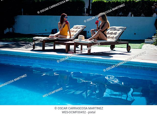 Two beautiful women relaxing on a terrace next to the pool