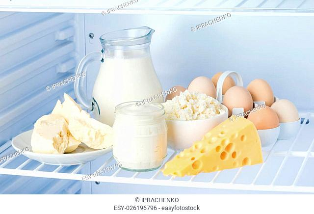 eggs and tasty healthy dairy products in the refrigerator: sour cream in the bank, cottage cheese in bowl, eggs, cheese, butter on a saucer and milk in a jar