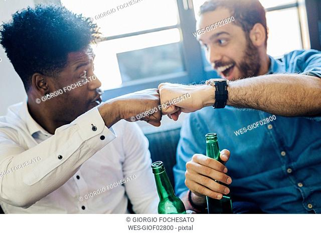 Excited friends with beer bottles sitting on the sofa bumping fists