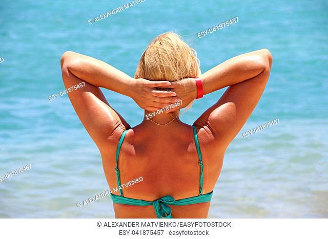 Girl sunbathing in sun during vacation on background of azure sea. Woman enjoying relaxing at sea. Woman enjoying sun, freedom and life