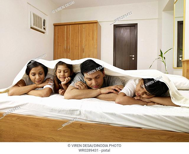 Parents with children under bed sheet sleeping on bed in bedroom MR702R,MR702S,MR702T,MR702U