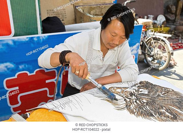 Mature man painting on a piece of cloth with a soldering iron, HohHot, Inner Mongolia, China