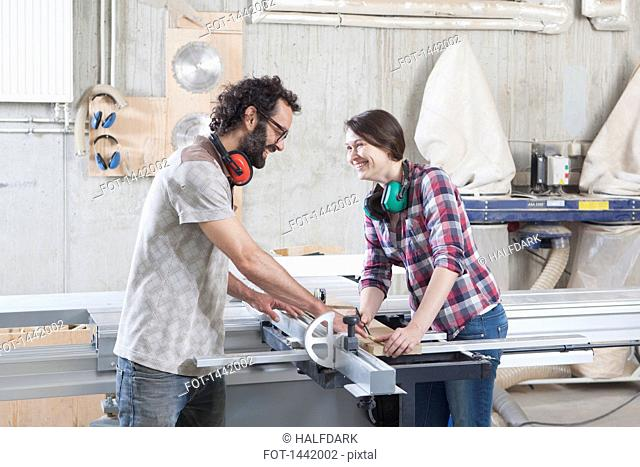 Side view of laughing coworkers using a sliding table saw in workshop