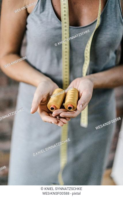 Woman with tape measure holding cotton reels