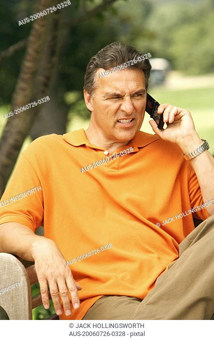 Close-up of a mature man talking on a mobile phone and looking frustrated