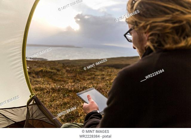 A man sitting in the shelter of a tent looking out, holding a digital tablet