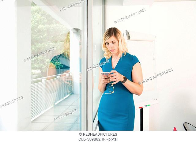 Woman texting on mobile phone in office