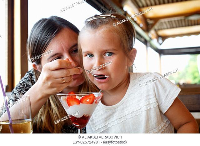 Mother feeds his daughter delicious sweet ice cream with strawberries in a restaurant. Shallow depth of field. Focus on the child's face