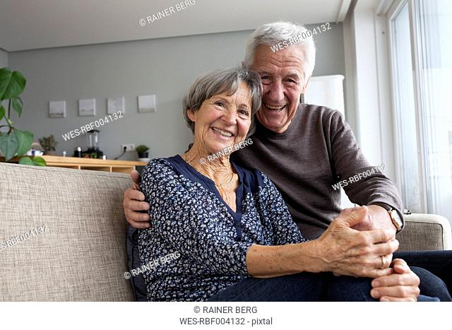 Happy senior couple sitting on the couch in the living room holding hands
