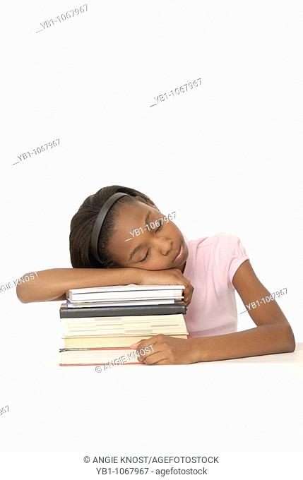 Student falling asleep on stack of books