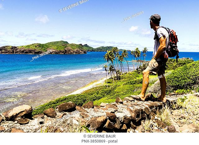 Man looking at the sea and an island, Petit Nevis, Saint-Vincent and the Grenadines, West Indies