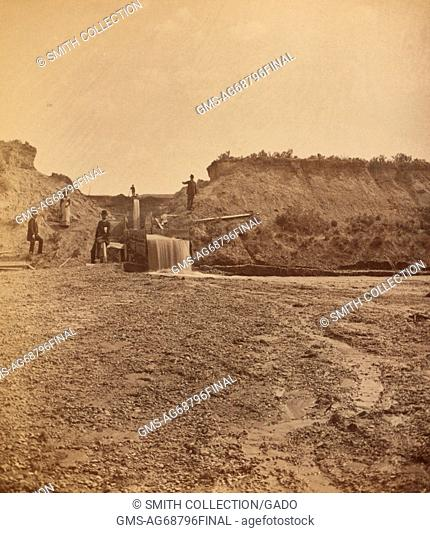 A photograph of four men and a woman near a sluice gate, three of the men men are in the foreground and are all dressed in formal suits and hats while the woman...