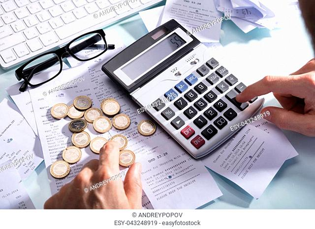 Businessperson's Hand Calculating Receipt With Coins And Eyeglasses On Desk